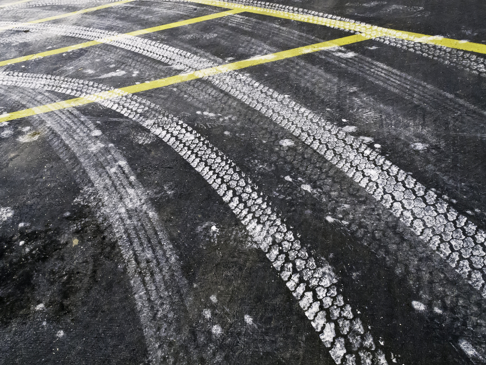 Automotive tire tracks from road salt on asphalt pavement in winter, northern Illinois